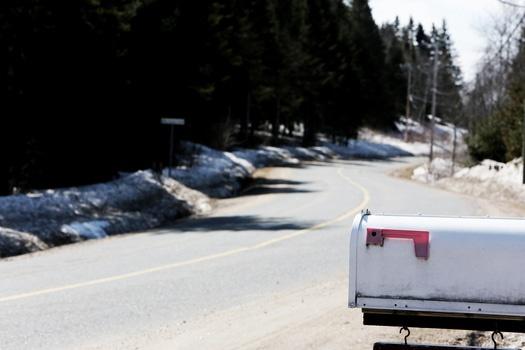 White Metal Mailbox Near Grey Asphalt Road at Day Time