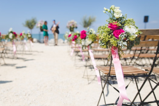 Black Metal Base Wooden Chairs Arranged in Rows and Columns With Floral Decorations Under Blue Sky during Day T Ime