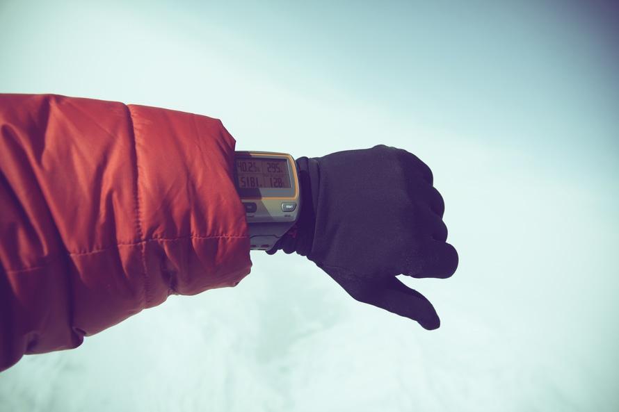 Persona en la chaqueta roja y negro usando guantes gris reloj digital
