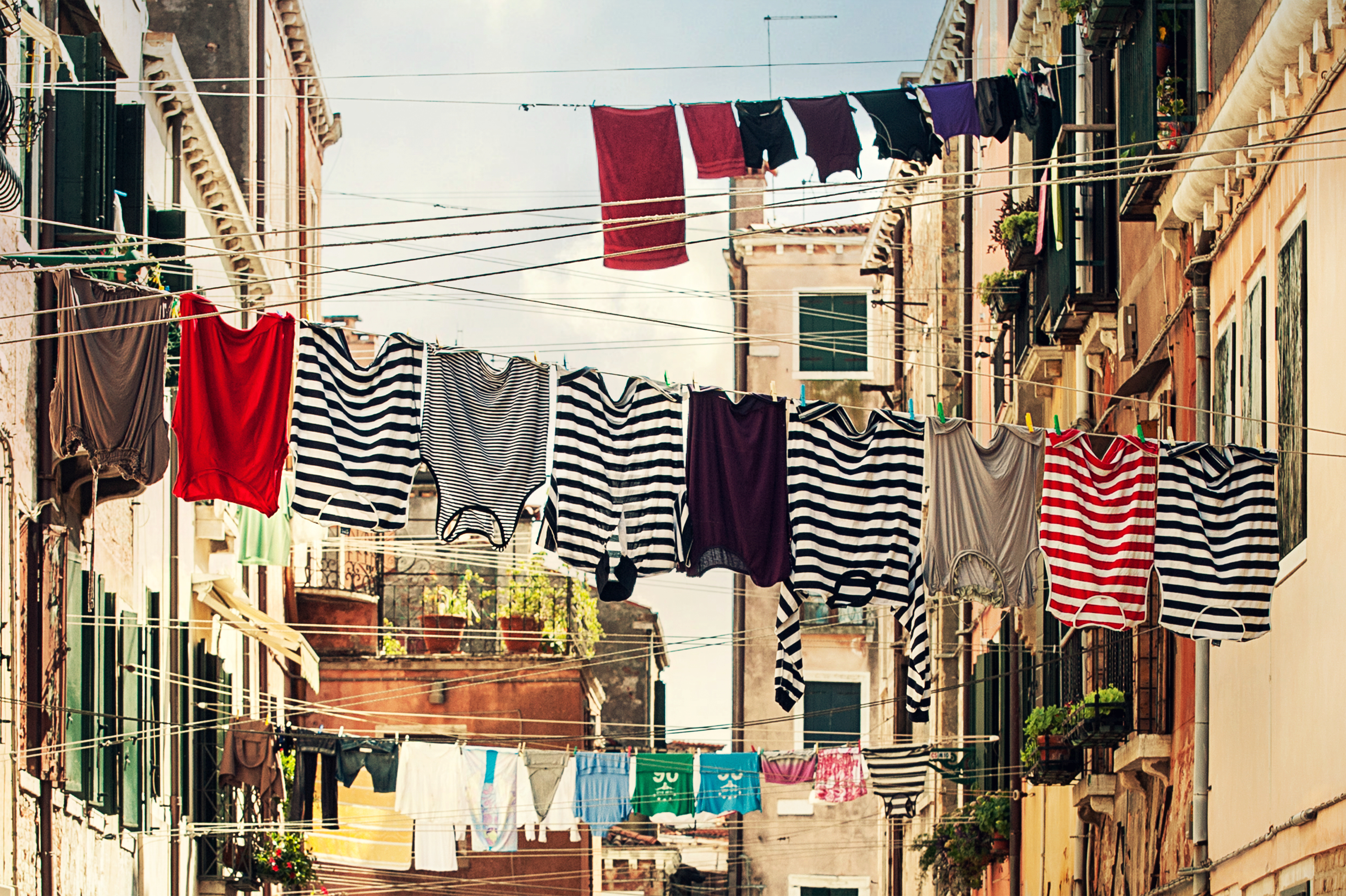 striped shirt hanging on gray wire between beige painted wall free download