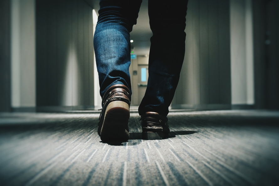 Person in Blue Denim Fitted Jeans Walking Through Hallway