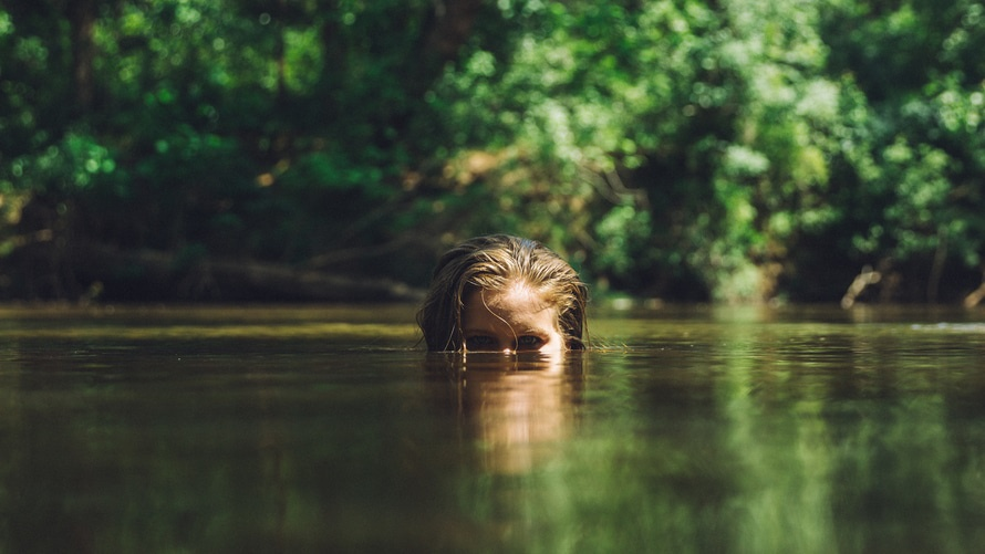 Blonde Woman's Head Peeking Up from the Water from the Eyes Up