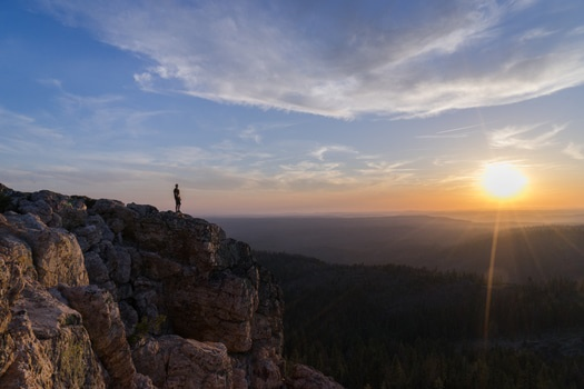 Man Standing on Cliff Watching Sunrise