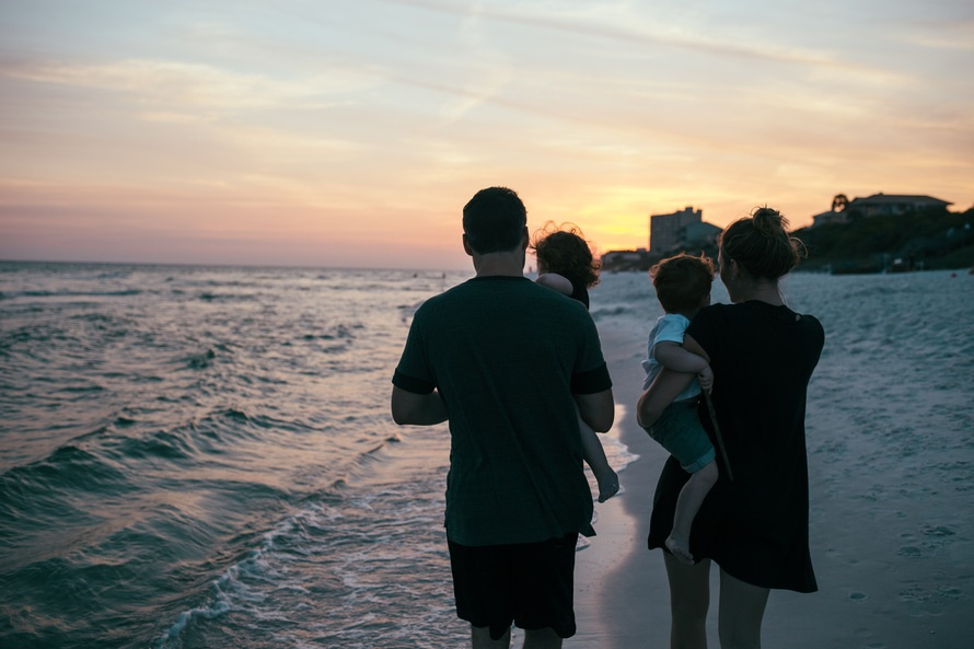 Woman in Black Shirt Carrying His Son in the Seashore during Sunset