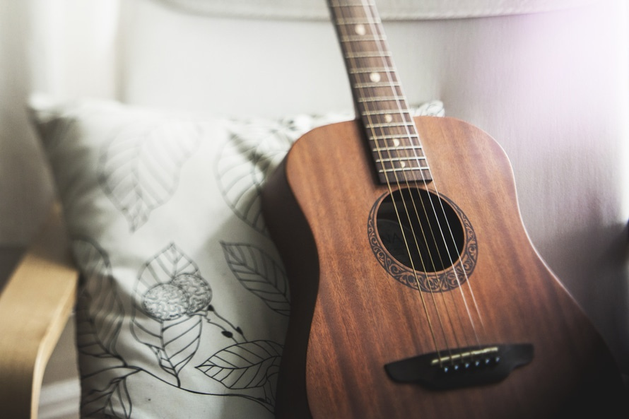 Shallow Focus Photography of Brown Acoustic Guitar on White and Black Leaf Print Pillow