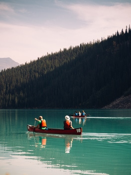 Group of People Riding a Row Boat in a Body of Water Surrounded by Trees