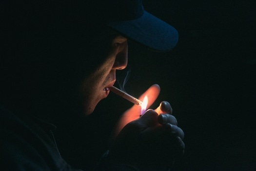 Man in Black Cap Lighting Cigarette during Nighttime