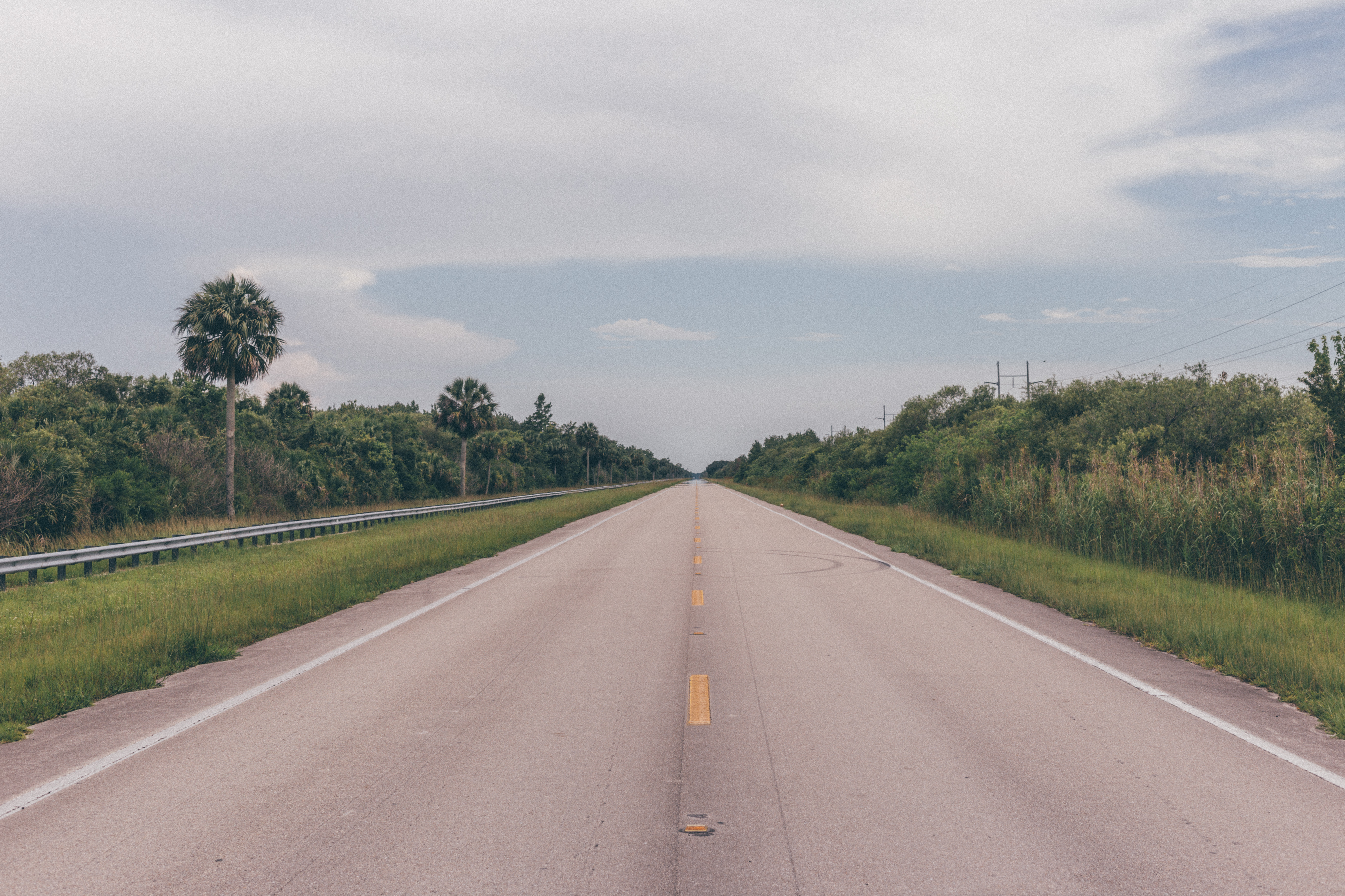 Open Road Highway With Green Grass And Blue Sky With An Asphalt