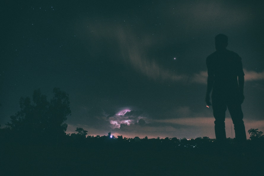 Silhouette of Man Standing Distance Trees during Night Time