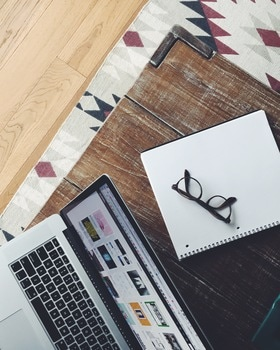 Black Frame Eyeglasses on Top of White and Black Spiral Notebook Beside Macbook Pro on Brown Wooden Table