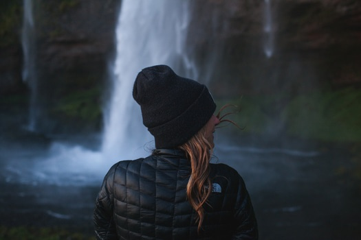 Blonde Haired Woman in Black Bubble Jacket and Black Knit Hat Beside Waterfall