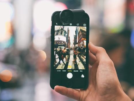 Human Taking Photo of People Walking in Pedestrian Lane during Daytime