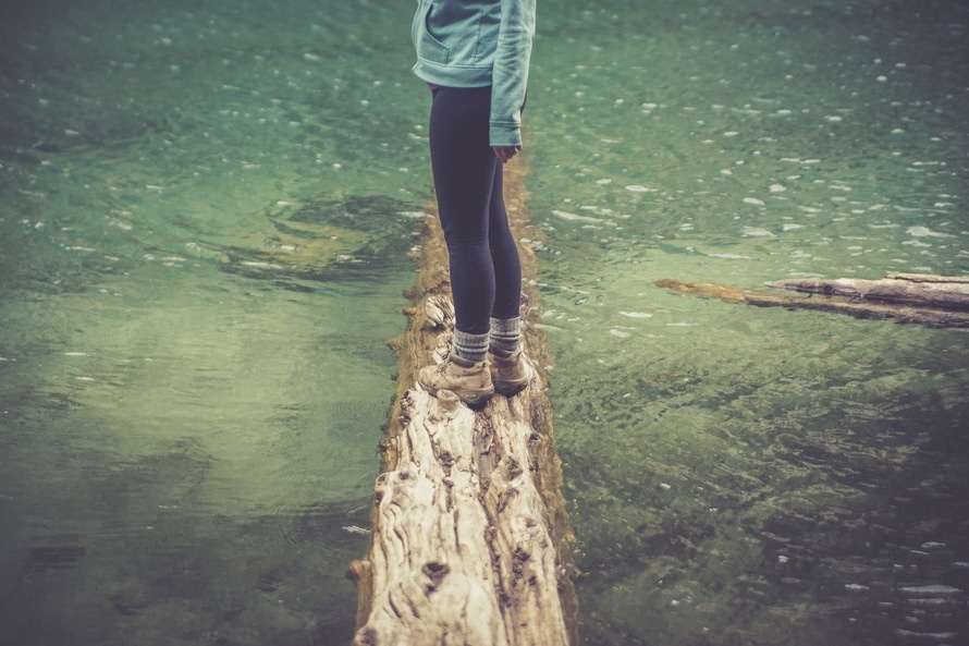 Person Standing on a Brown Wood Log Floating on a Body of Water