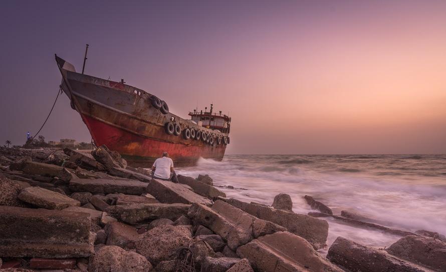 Azul Rojo y Negro Foto de una nave y un hombre sentado en una piedra cerca de la costa