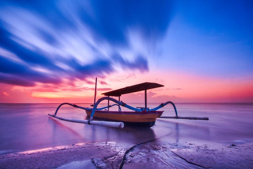 Marrón azul y blanco de madera del barco durante la puesta del sol anaranjada