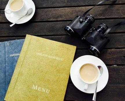 White Ceramic Tea Cup on White Saucer Near Menu Book