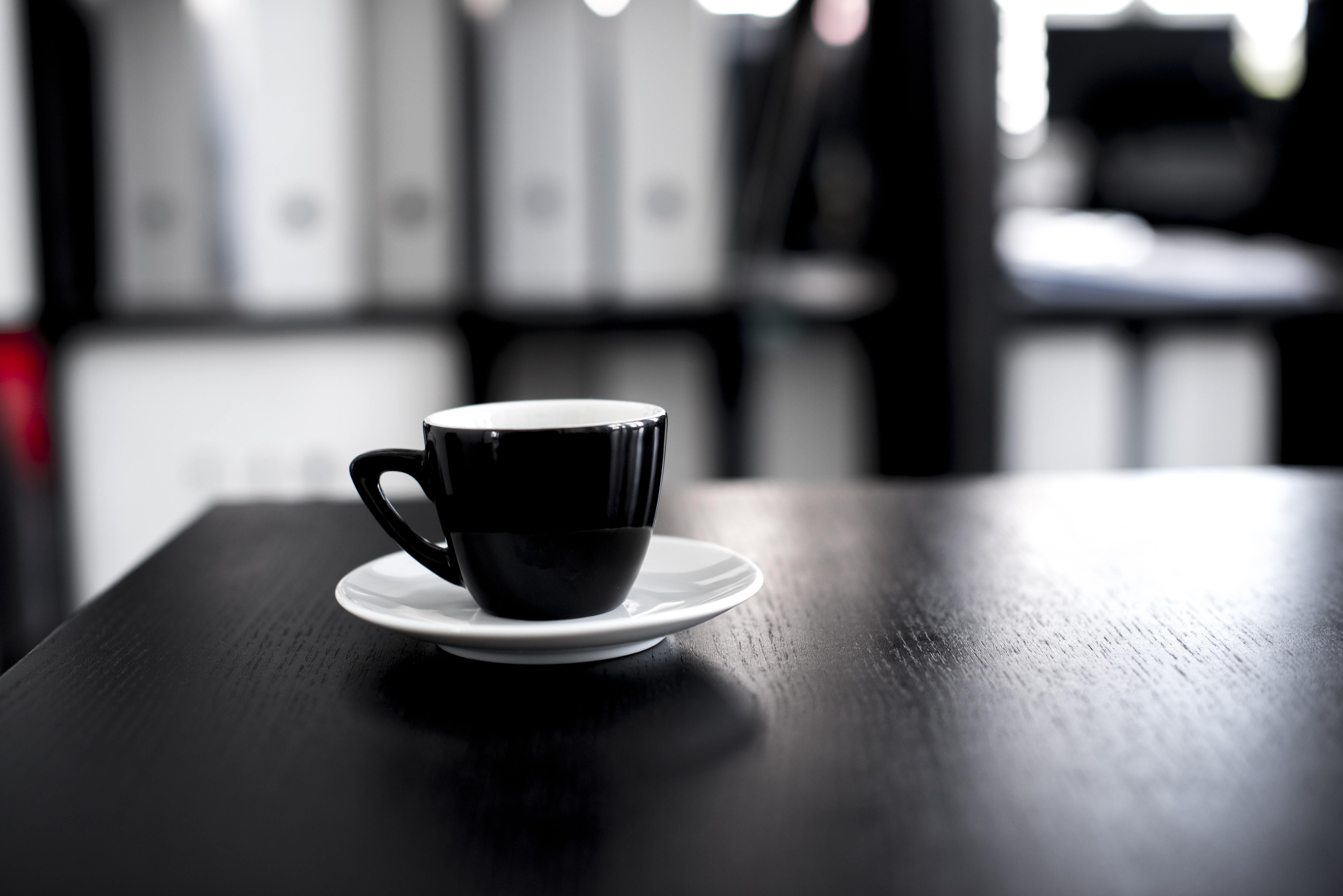 Black and white ceramic tea cup with saucer on black wooden table free download geotapseo Gallery