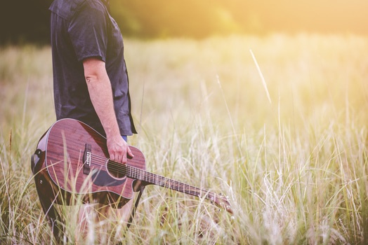 Man in Black Button Up Shirt Holding Brown Acoustic Guitar on Tall Grass during Daytime