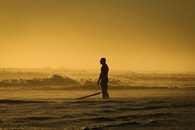 Man Standing on Seashore While Holding His Surfing Board during Sunset