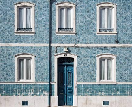 Blue Wooden Door With White Door Frame on Blue Concrete Building