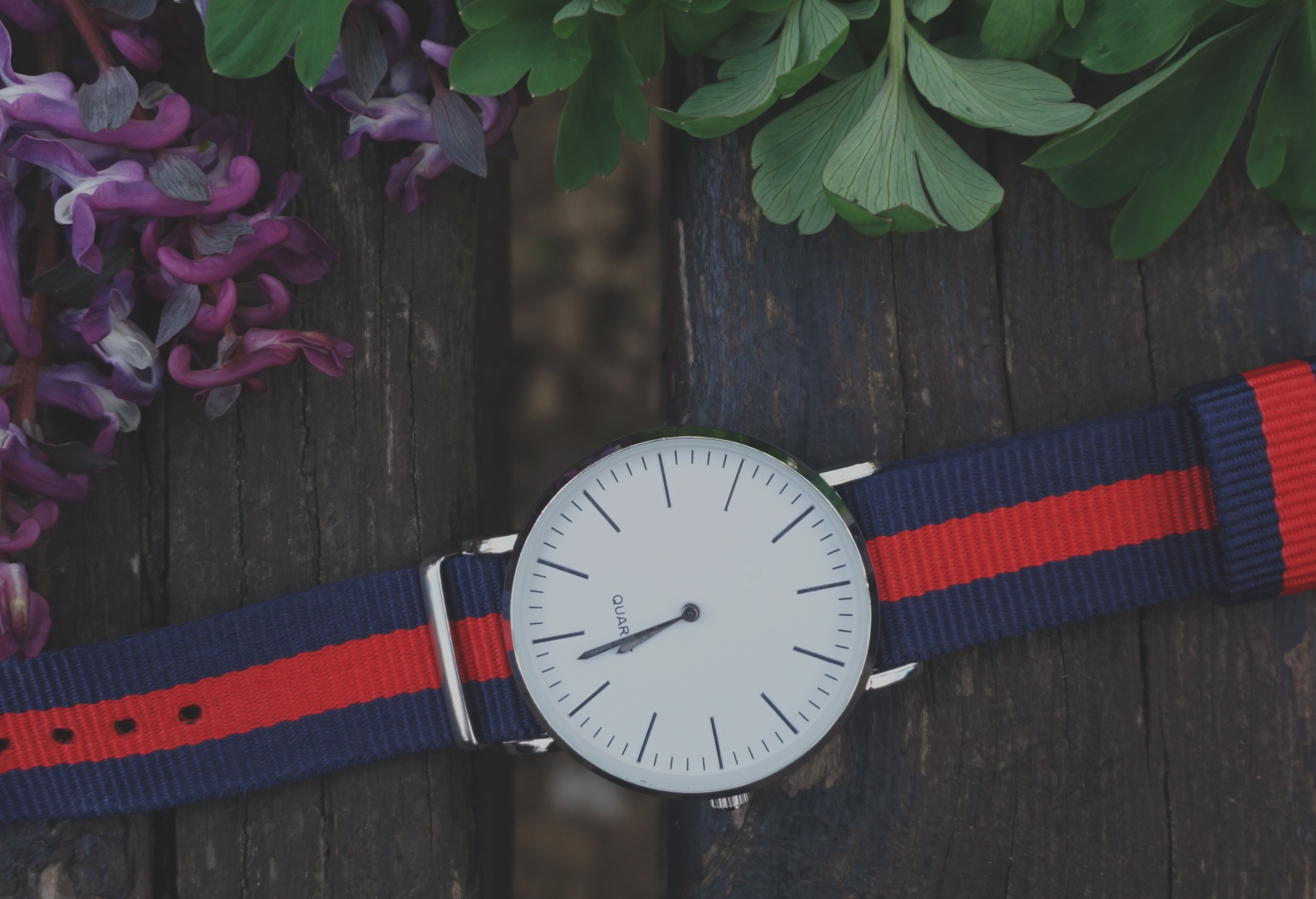 blue and red strap silver round analog watch beside purple