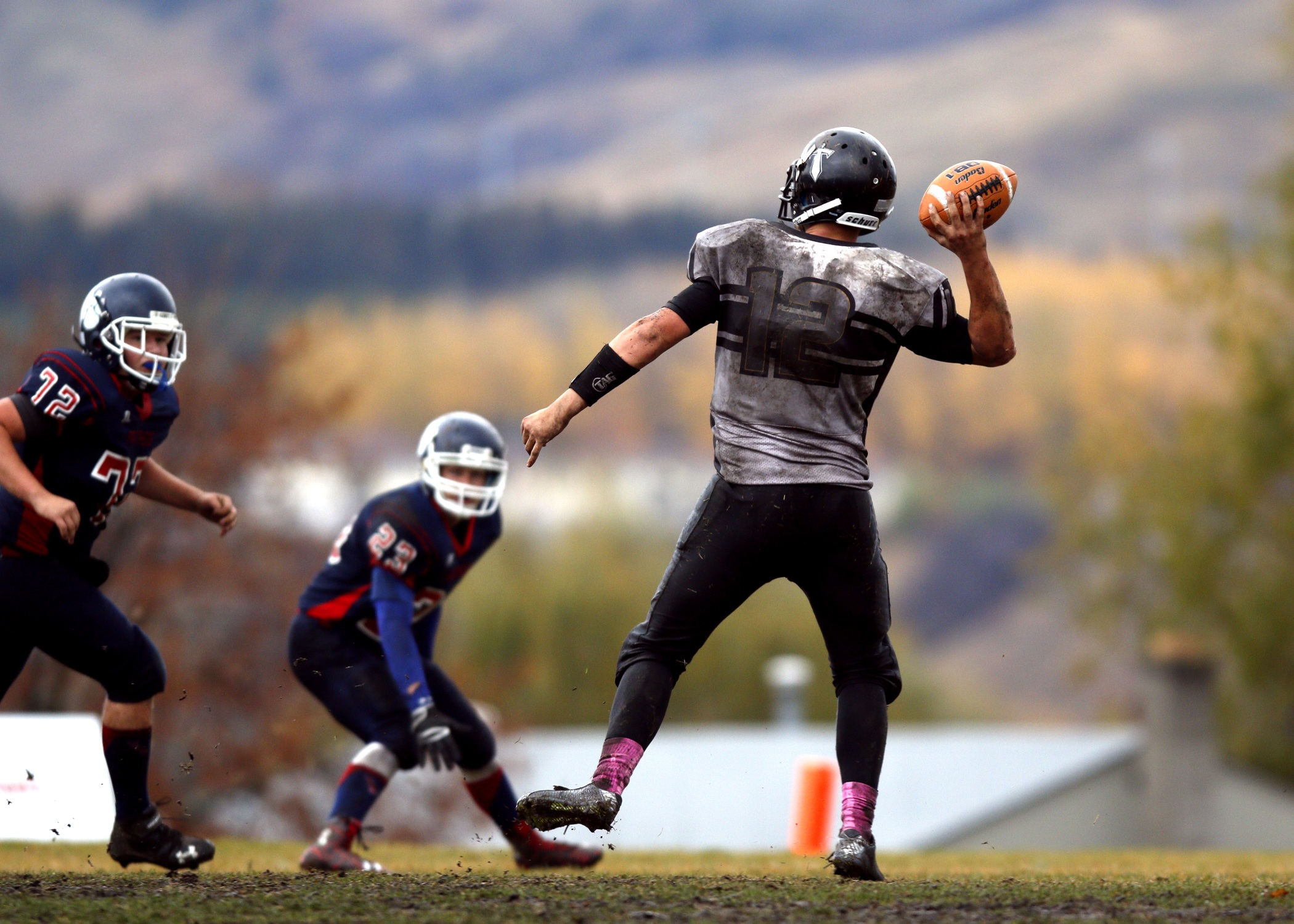 2 football player running after person holding football during daytime in shallow focus