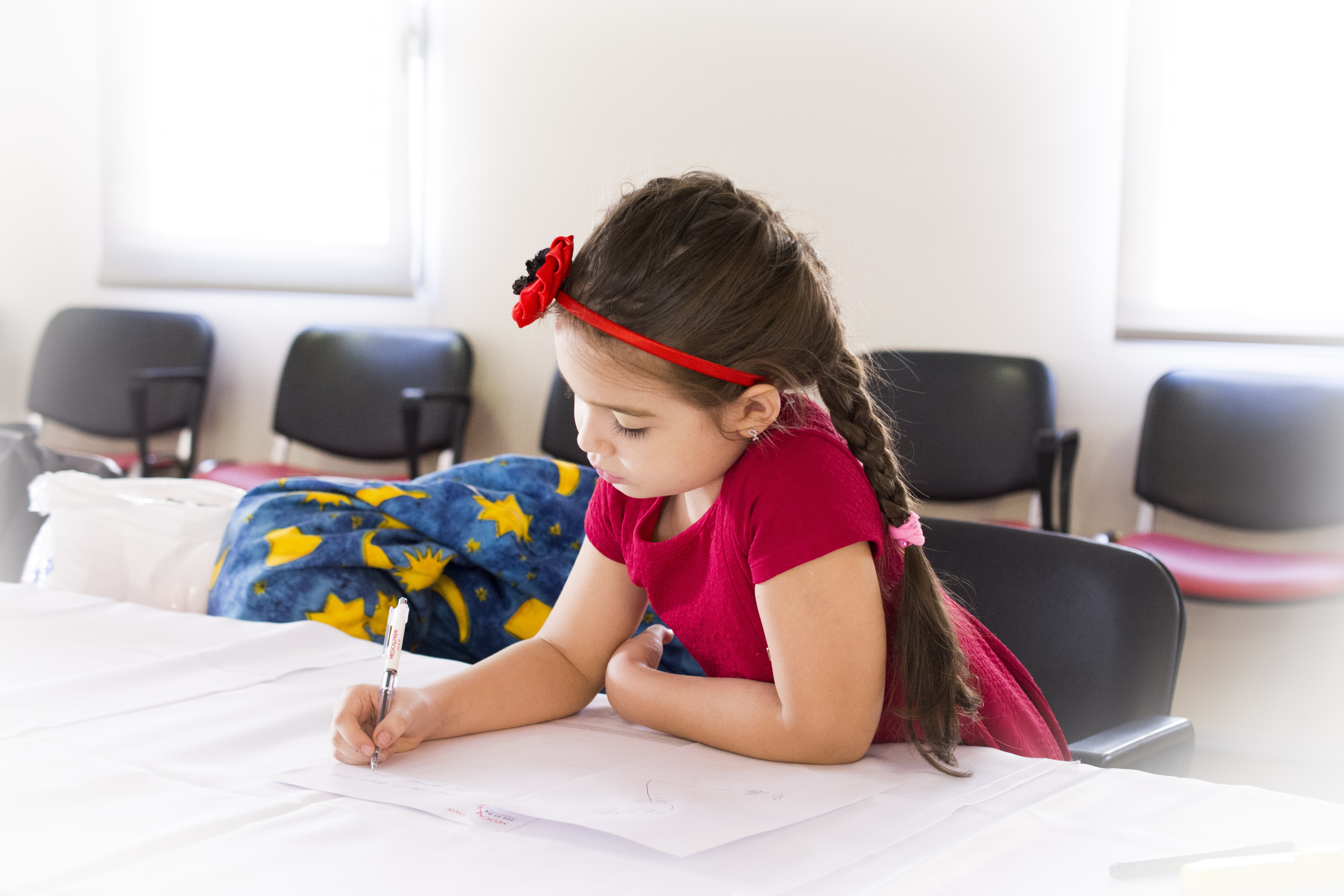 girl in red short sleeve dress and flower headband holding pen and writing on paper on