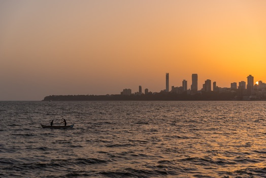 2 Person on the Boat on the Ocean in Front Urban City during Golden Hour
