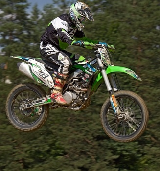 Man in Green White and Black Mtx Suit on Green and White 303 Dirt Motorcycle in the Air