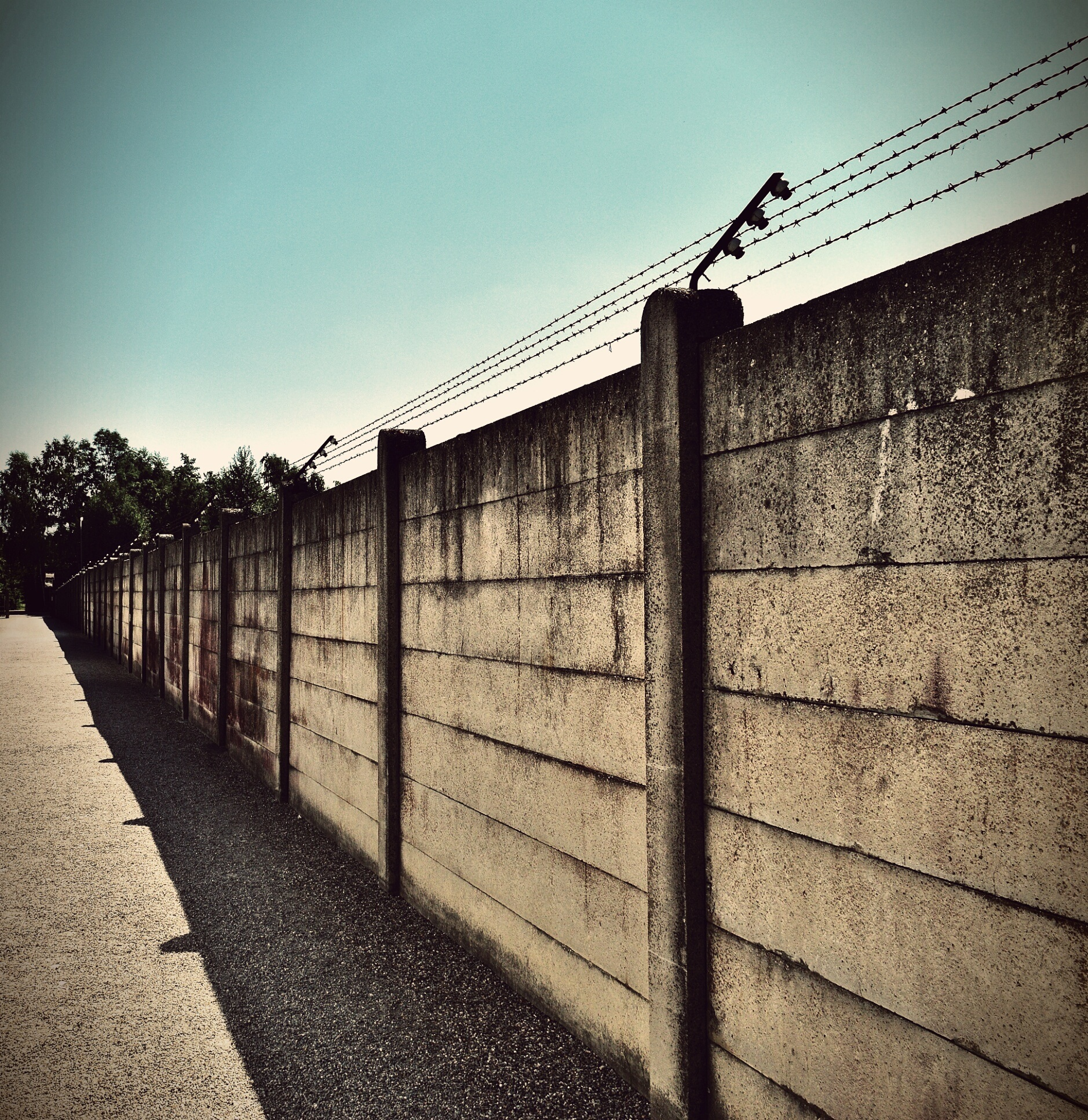 Beige and black concrete wall with barbwire on top · free