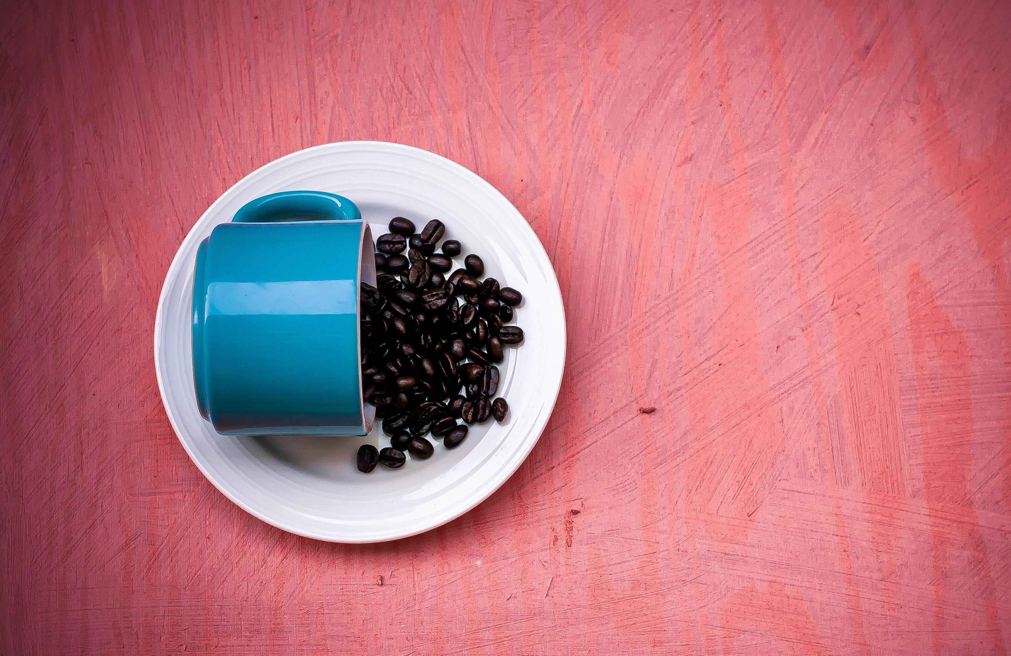 Blue ceramic tea cup with beans on a white plate