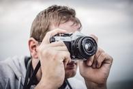 Man Holding Black Silver Bridge Camera Taking Photo during Daytime