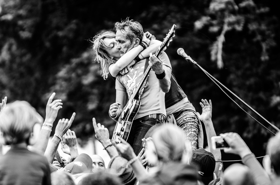 Grayscale Photo of a Woman Kissing a Man Playing Guitar