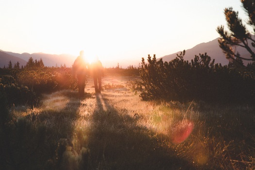 2 People Walking on Grass Field in Front of Mountain during Sunrise