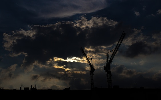 Silhouette of Tower Crane Under Blue and Black Cloudy Sky during Nighttime