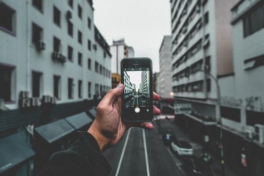 Man Holding Smartphone Capturing Roadway