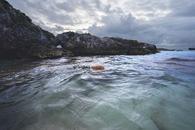 Rocky Cliff Near Calm Sea Under Gray Cloudy Sky