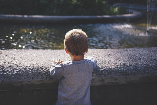 Boy in Gray Top Standing in Front of Water Fountain