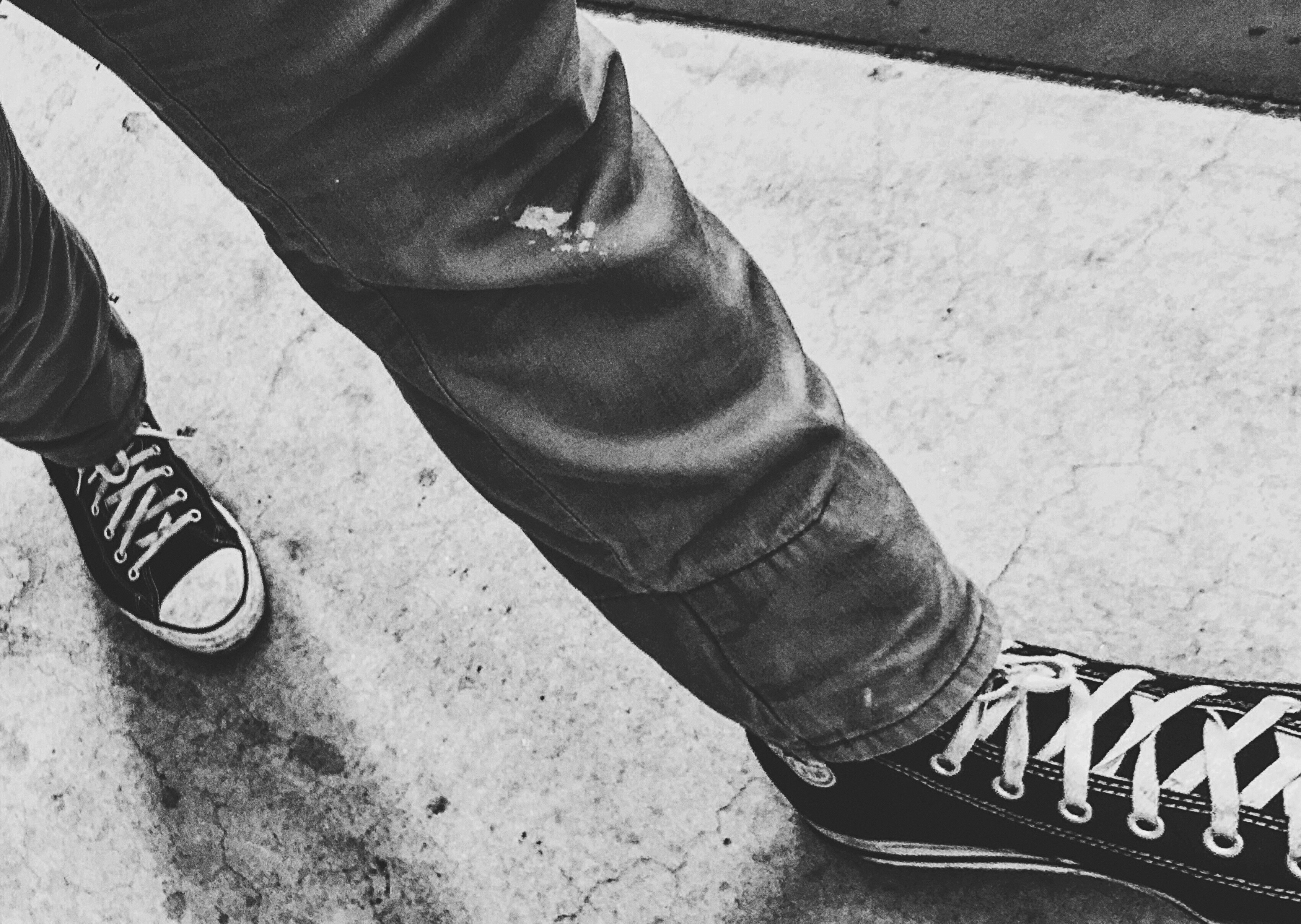 person walking wearing black shoes in grayscale