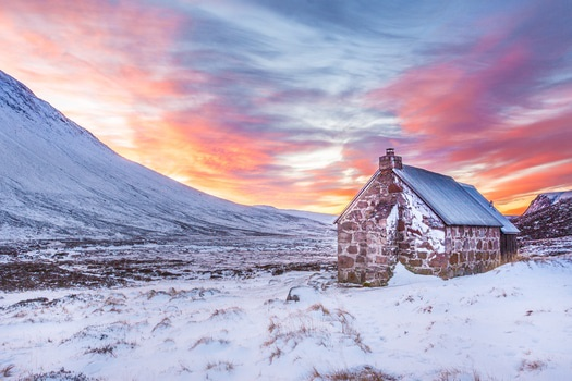 Brown House Surrounded by Snow Covered Field Near Snow Covered Mountain Under Yellow Blue and Orange Sunset