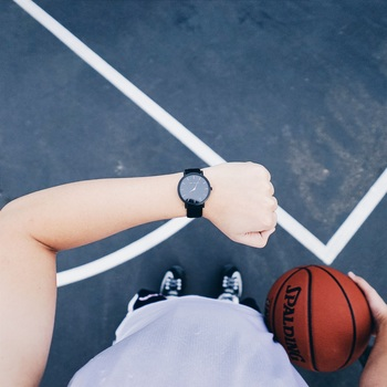 Person Wearing Black Round Analog Watch on Left Wrist While Holding Basketball on Right Hand