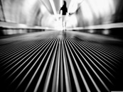 Greyscale Photography of Man Walking on Tunnel