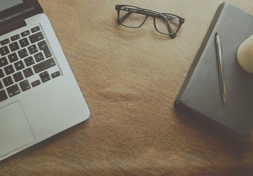 Macbook Pro Beside Black Framed Eyeglasses on Brown Wooden Surface