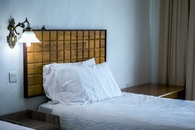 White Bedding Cover Beside Brown Wooden Side Table