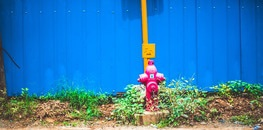 Pink Steel Water Pump Behind Blue Fence