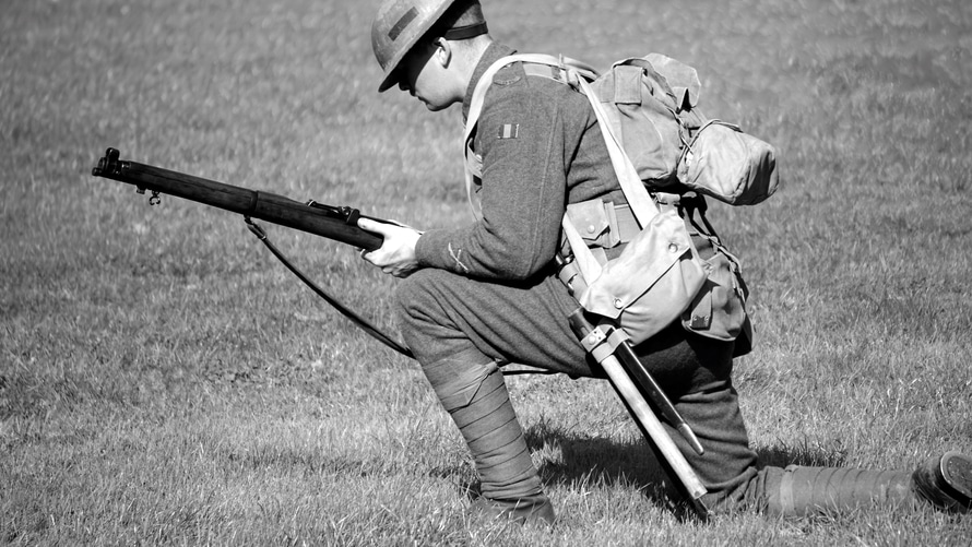 Man in Soldier Suit Holding Gun Knees Down in the Ground