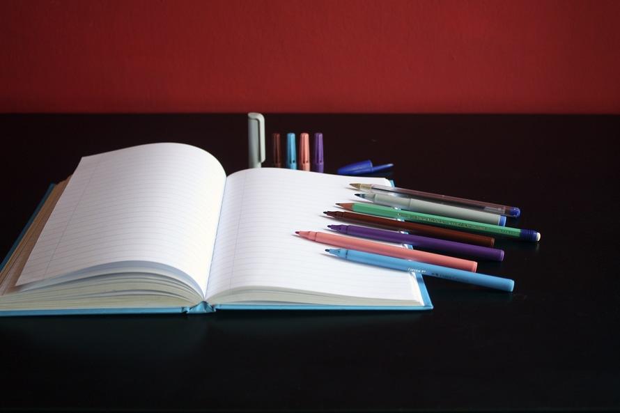 Blank Notebook Beside Color Pens