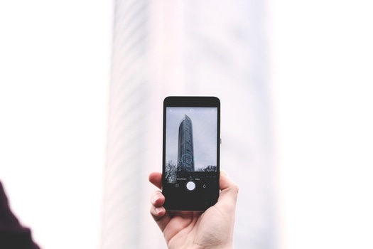 Free stock photo of hand, smartphone, taking photo, building