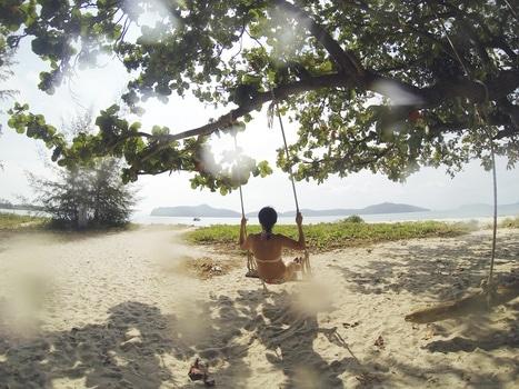 Woman in White Bikini Using Swing Under Green Leaf Tree during Daytime