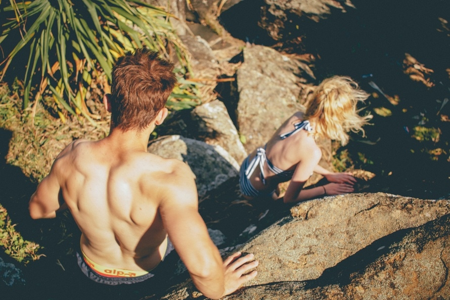 Topless Man Behind Woman Walking on Gray Rock Formation during Daytime